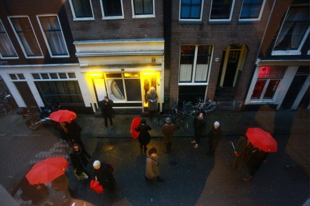 Straatbranding. De korsjesportsteeg wordt overstroom door bestuurders met paraplu's voorzien van I Amsterdam logo.
